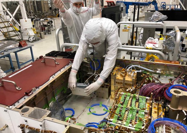 Technicians installing the Mastcam-Z Digital Electronics Assembly (DEA) into the body of the Mars 2020 mission's Perseverance rover at JPL in April, 2019.