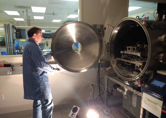 Mastcam-Z lead systems engineer Mike Caplinger inspects the installation of the flight cameras in the thermal vacuum chamber at Malin Space Science Systems in May, 2019.