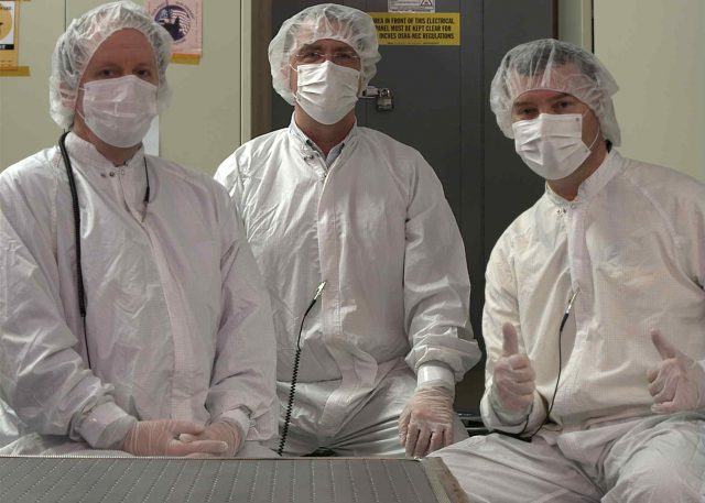 During the functional checkout required as part of delivery of the cameras to the rover at JPL, P.I. Jim Bell (right), Instrument Manager Mike Ravine (middle), and Deputy P.I. Justin Maki (left) pose for a clean room portrait taken with the left Mastcam-Z flight camera.