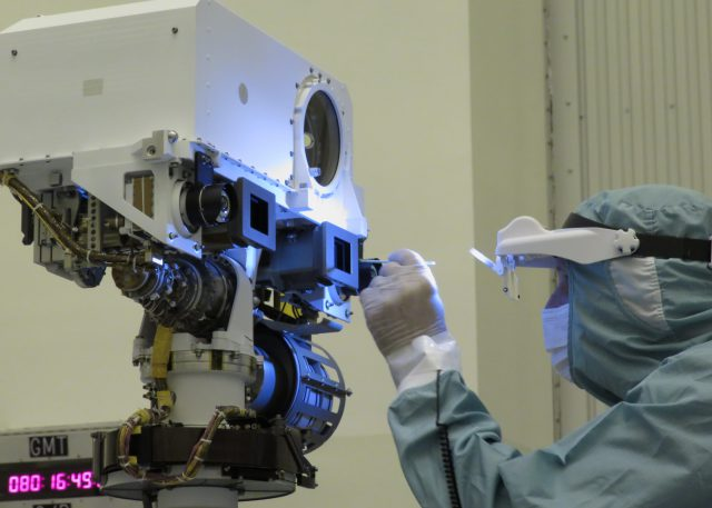 JPL optical technician Jerry Mulder performs a final inspection and swab cleaning of the front optics of the Mars 2020 mission's Perseverance rover Mastcam-Z cameras at the Kennedy Space Center in March, 2020.