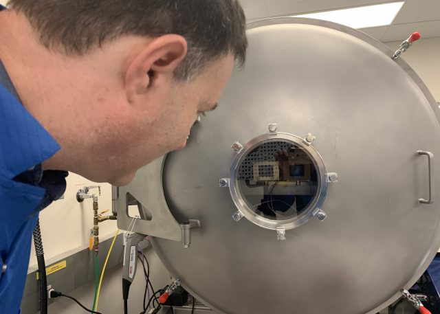 Principal Investigator Jim Bell looking into the vacuum chamber at Malin Space Science Systems, where the flight cameras were tested. The front surfaces of both cameras are visible behind the vacuum chamber window.